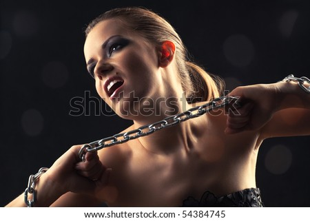 Young fashion woman breaking metallic chain. - stock photo