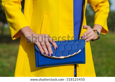 Young fashion woman hold blue handbag clutch - stock photo