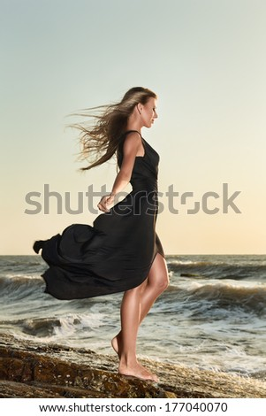 Young fashion woman in a luxurious long dress posing in front of sea