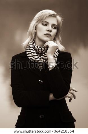 Young fashion woman in black coat walking outdoor - stock photo