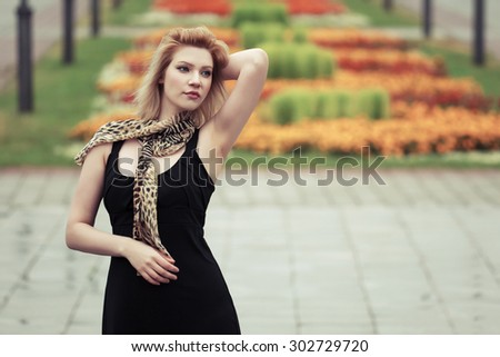 Young fashion woman in black dress outdoor - stock photo
