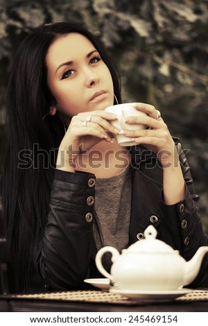 Young fashion woman in leather jacket drinking a tea  - stock photo