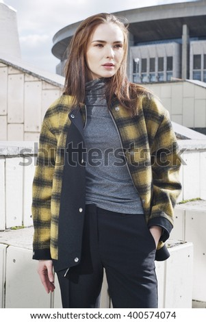 young fashion woman in plaid jacket in street, hand in pocket - stock photo