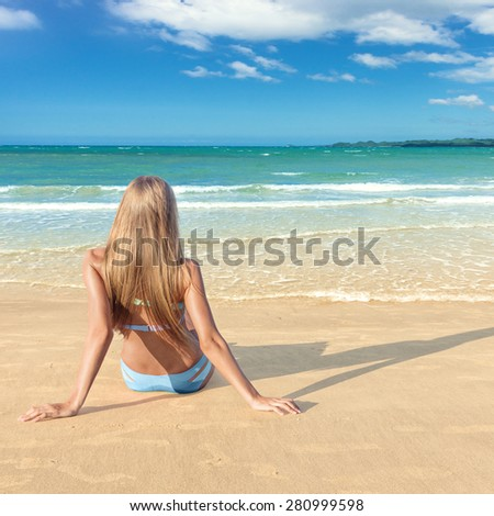 Young fashion woman looking on sea at tropical beach