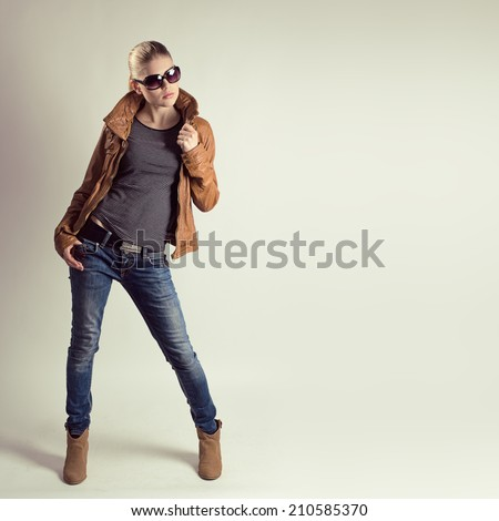 Young fashion woman model wearing stylish casual clothes. Beautiful glamour Caucasian female in sunglasses posing in studio.  - stock photo