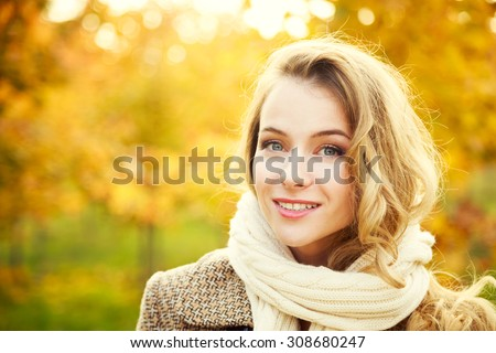 Young Fashion Woman on Autumn Background in Sunny Day. Smiling Happy Girl Portrait. Toned Photo with Copy Space.