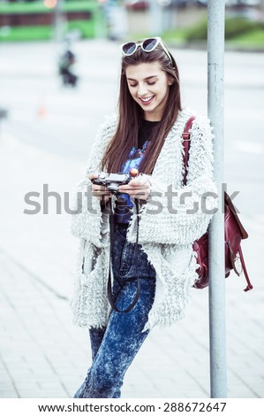 Young fashion woman photographer flirting on the background of old city street. Outdoors, lifestyle. doing selfie