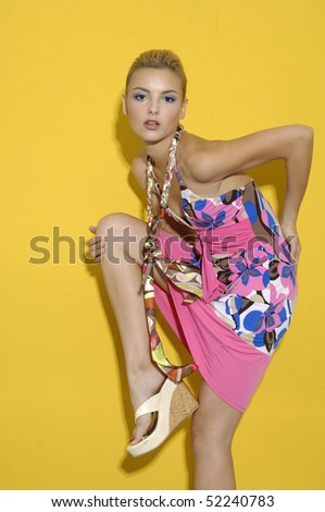 Young fashion woman posing on yellow background