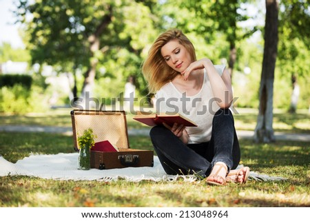 Young fashion woman reading a book in a city park - stock photo