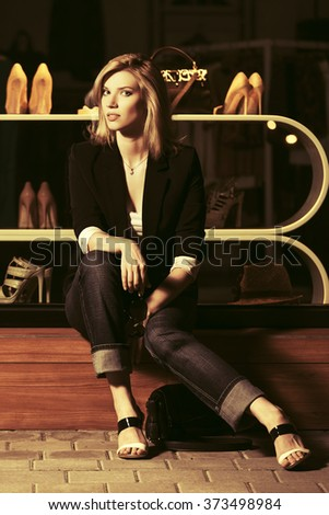 Young fashion woman sitting on the mall window - stock photo