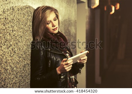 Young fashion woman using tablet computer at the wall. Female fashion model in black leather jacket - stock photo