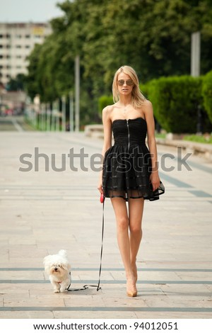 young fashion woman, walking her dog in the park - stock photo