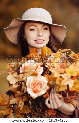 Young fashion woman  walking in autumn park with a bouquet of fall leaves of maple and oak autumn roses. - stock photo