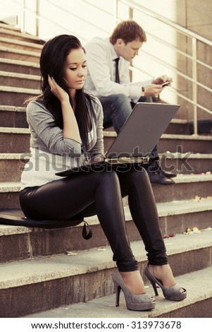 Young fashion woman with laptop on the steps - stock photo