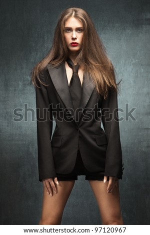 young fashion woman with long brown hair in black tuxedo jacket, tie and shorts, stand in front blue grunge wall