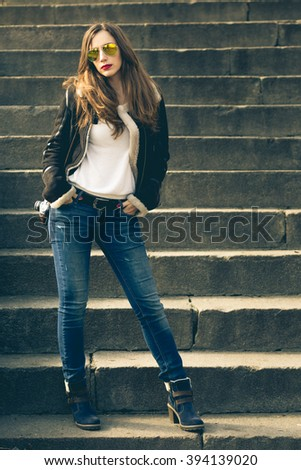 Young fashion woman with photo camera stands on the stairs. Attractive stylish caucasian girl in city outdoors - stock photo