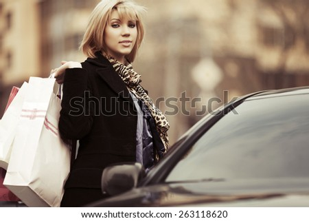 Young fashion woman with shopping bags next to car - stock photo
