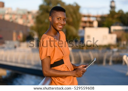 Young fashionable african woman with tablet outdoor, New York, Manhattan view, skyline