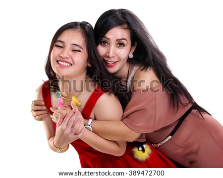 Young fashionable Asian mother hugging her cute smiling daughter from behind, isolated on white background - stock photo
