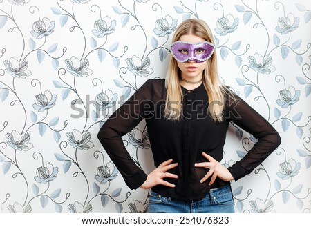 Young fashionable blonde woman posing in mask against a wall with vintage wallpapers pattern