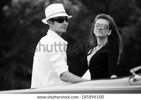 Young fashionable couple at the classic car - stock photo