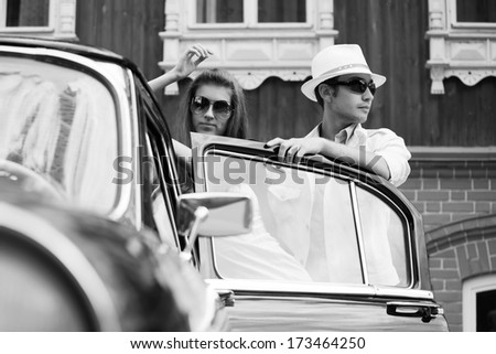 Young fashionable couple at the retro car - stock photo