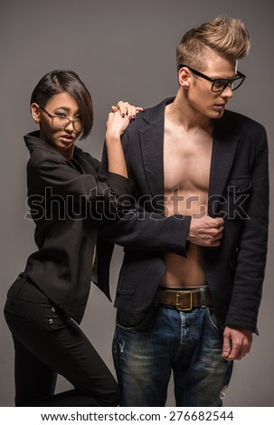 Young fashionable couple dressed casual posing in the studio on dark background. Fashion portrait. - stock photo