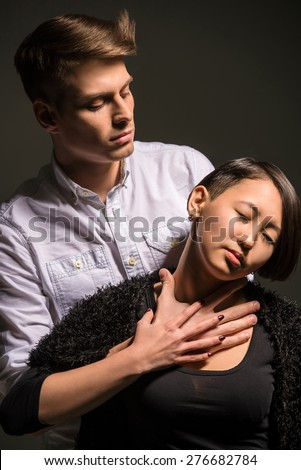 Young fashionable couple dressed casual posing in the studio on dark background. Fashion portrait. Jealousy. - stock photo