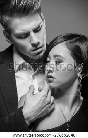 Young fashionable couple dressed in formal clothing posing in the studio. Black and white fashion portrait. Passion. - stock photo