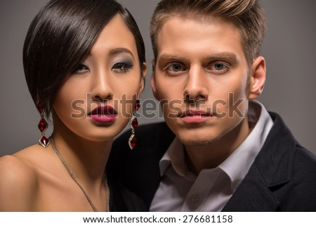 Young fashionable couple dressed in formal clothing posing in the studio on dark background. Fashion portrait. - stock photo