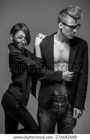 Young fashionable couple in glasses and tuxedos  posing in the studio. Black and white fashion portrait. Passion.