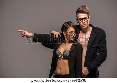 Young fashionable couple in glasses and tuxedos  posing in the studio on dark background. Fashion portrait. Passion. - stock photo