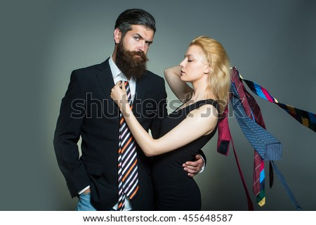 young fashionable couple of woman with pretty face and blonde hair and handsome bearded man with long beard in black jacket and tie in studio on grey background