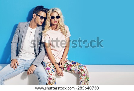 Young fashionable couple on blue background - stock photo