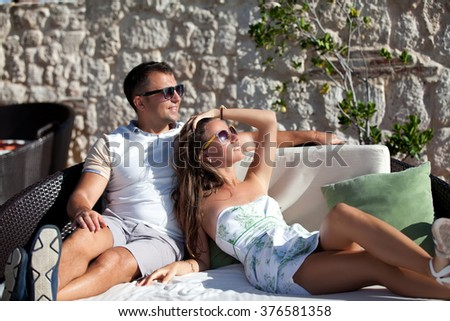 Young fashionable couple relaxing on couch. Beautiful family is at resort terrace. Happy tourists is spending leisure time during vacation. - stock photo