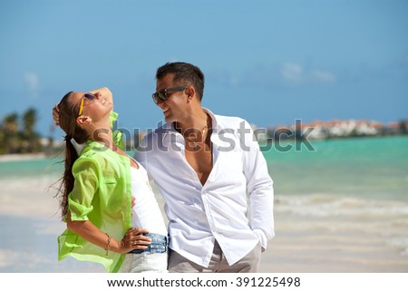 Young fashionable couple relaxing on the beach. Happy tourists is spending leisure time during vacation. - stock photo