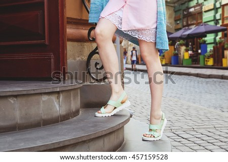 Young fashionable girl in light green leather sandals on the stone steps in the city. Summer clothes. Woman walking in the city. - stock photo