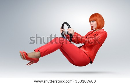 Young fashionable girl in red driver car with a wheel, auto concept