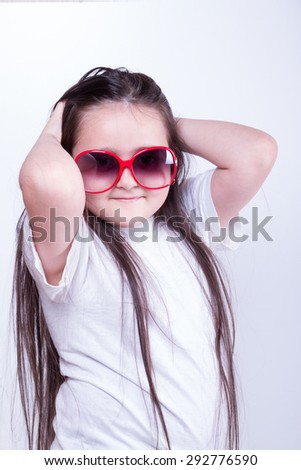 Young fashionable girl in sunglasses holding his hands behind his head and smiles