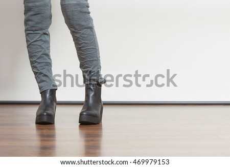 Young fashionable girl with long legs wearing black shoes on platform. Fashion in winter time.