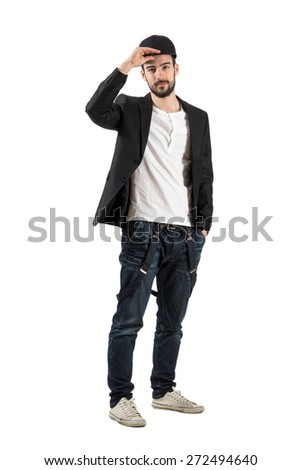 Young fashionable guy holding putting baseball cap on his head. Full body length portrait isolated over white background.