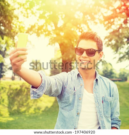 Young fashionable hipster Hispanic man with sunglasses taking a selfie outdoors on sunny summer day. Modern lifestyle concept. - stock photo