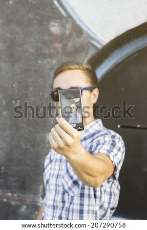 Young fashionable hipster man with sunglasses taking a selfie outdoors - stock photo