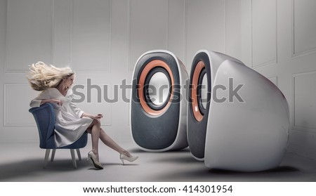 Young fashionable lady listening to big loudspeakers - stock photo