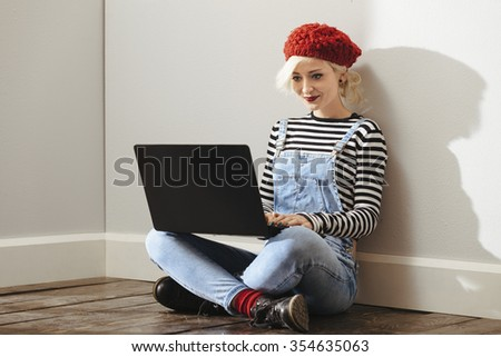 young fashionable lady sitting in an empty room with wooden floor and using her laptop