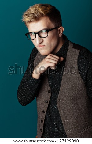 Young fashionable man in a shirt, vest and glasses on aqua background