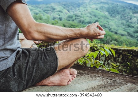 Young fashionable man meditating in the gazebo on the background of the mountains in Bali