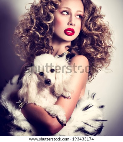 Young fashionable queen with crown and mantle with dog - stock photo