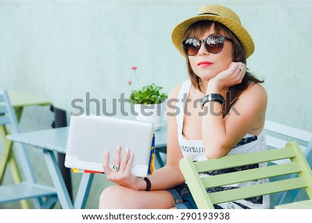 Young fashionable tourist girl sitting and thinking in a European street cafe with tablet while on vacation. - stock photo