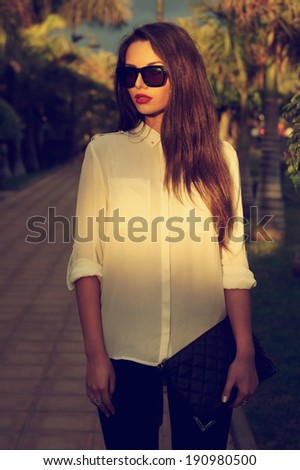 Young fashionable trendy girl posing at tropical alley between palms in evening soft light.  toned portrait of young woman in black jeans, white blouse and sunglasses holding handbag - stock photo